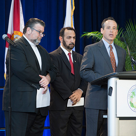 Three men standing by a podium, one of them speaking